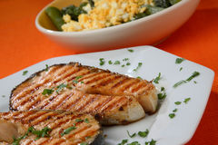 Two grilled salmon steaks with herbs close up Royalty Free Stock Photos