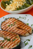 Two grilled salmon steaks with herbs close up Stock Images