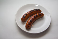 Two grilled sausages on white Royalty Free Stock Image