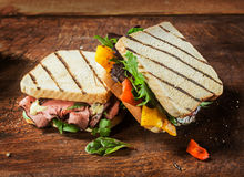 Two grilled toasted sandwiches at a BBQ. Displayed on a rustic wooden table one with a rare roast beef and herb filling and the other with cheese, rocket and Stock Photos