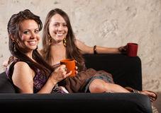 Two Grinning Ladies Sitting on Sofa. Two grinning ladies sitting on a sofa holding mugs royalty free stock photography