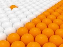 Two groups of 3d balls. 3d rendering of orange and white spheres. One orange sphere included between the whites Royalty Free Stock Photography