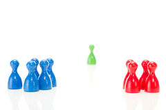 Two groups of meeples against the green one Stock Photos