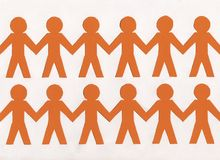 Two groups of orange paper men on white background. Business background stock photos