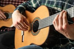 Two guitar players with classic guitars stock images