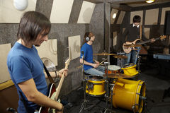 Two guitarists and drummer working in studio. A rock band. two musicians with electro guitars and one drummer working in studio Royalty Free Stock Images