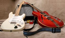 Two guitars. The red and cream electric guitars lay on the amplifier Royalty Free Stock Image