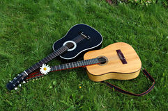 Two guitars on green lawn. A view of a 6 and 12-string guitar lying together on a green lawn after a concert royalty free stock photography
