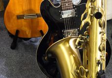 Two guitars and a saxophone Stock Images