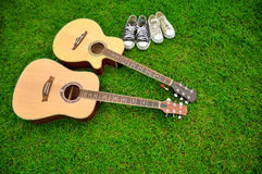 Two guitars and two pairs of shoes on bright green grass texture Royalty Free Stock Photography