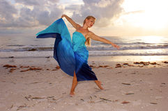 Two gulls and a woman. An attractive adult woman is dancing on the beach with the sun behind her and two seagulls in the background, she appears to be carefree Royalty Free Stock Photos