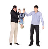 Two gusd holding little boy upside down Stock Photo