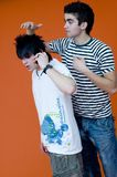 Two Guys. Two teenaged boys, one with spiky hair and talking on telephone, wearing dreamstime shirt, the other one adjusting his friend's hair Royalty Free Stock Images