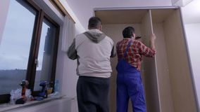 Two guys assembling the closet. Two men are assembling new furniture in freshly painted room. They use compact cordless drill-driver, hammer and various stock video