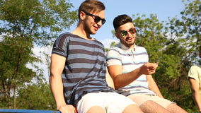 Two guys best friends are sitting on fencing, talking and laghing stock video footage