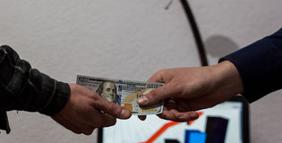 Two guys or businessmen trade exchange dollars from hand to hand Stock Image