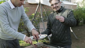 Two guys cook the meat on the grill outdoors. Friends at a barbecue during the weekend stock video footage