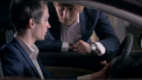 Two guys discussing the car in the showroom stock video footage