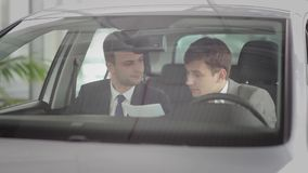 Two guys discussing the car specifications. Buyer and the salesman discussing the car specifications in motorshow stock video footage