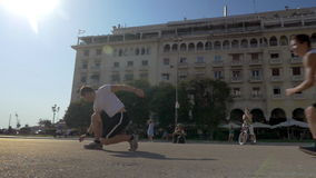 Two guys doing extreme tricks on the square. Slow motion steadicam clip of two teens doing extreme tricks on the city square. Boys turning cart-wheel and jumping stock video footage