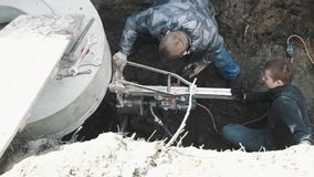 Two guys drill round hole in concrete manhole ring using industrial drill stock video footage