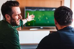 Two guys drinking beer watching football stock photo