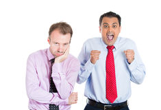 Two guys, an excited, optimistic one and a bored, annoyed one, standing next to each other Royalty Free Stock Photo