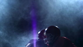 Two guys facing football bodies and diverging in the smoke. Slow motion stock footage