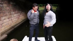 Two guys in fake muscle padded costumes dance in boat moving under bridge.