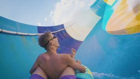 Two guys on the family water slide going down in slow motion. Two guys on a bright sunny day on the water slide ride down in slow motion (120fps stock video footage