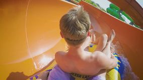 Two guys on the family water slide going down in slow motion. Two guys on a bright sunny day on the water slide ride down in slow motion (120fps stock video