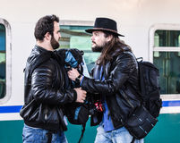 Two guys are fighting because they missed their train. Stock Photos