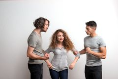 Two guys fighting over a girl, a studio shot. royalty free stock photography