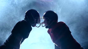 Two guys football player facing their helmets in the smoke. Slow motion. Two guys in the rugby protective gear face their helmets in the smoke. Smoky background stock footage