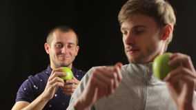 Two guys funny dancing holding green apples isolated in black stock footage