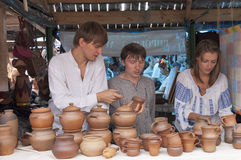 Two guys and a girl selling pottery. 18/08/2012. Ukraine. Sorochinskaya Fair. Handicrafts row of stalls . The famous annual fair is opening in the village of stock photography
