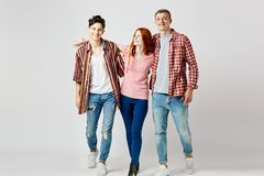 Two guys and a girl in stylish bright colorful clothes walk and smile on the white background in the studio stock images