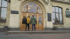 Two guys goes to the entrance of the university. Two students goes to the entrance of the university. Friends are discussing some educational material. Young stock video