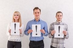 Two guys and a girl with light smiles are standing next to keep the sheets with exclamation marks on a gray background Stock Image