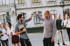 Two Guys. Greet. High Five. Group of Young People. Two Guys Greet High Five Group of Young People Courtyard University Students. Study Together Good Mood stock images