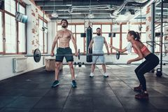 Two Guys In Gym Lifting Barbell. Supporting Girl royalty free stock photos