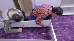 Two guys handle the bed frame with screwdrivers. Two men are assembling new furniture in freshly painted room. They use compact cordless drill-driver, hammer and stock video