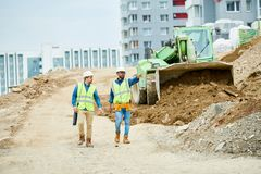 Men inspecting construction site. Two guys in helmets and waistcoats walking near digger and pointing at distance during inspection on construction site Stock Photography
