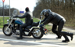 Two guys helped push bike stock photos