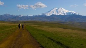 Two guys are hiking by the road in Caucasus mountains. Friends are going to mount Elbrus 4K UHD stock footage
