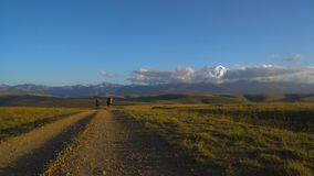 Two guys are hiking by the road in Caucasus mountains. Friends are going to mount Elbrus in clouds 4K UHD stock video footage