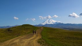 Two guys are hiking by the road in Caucasus mountains. Friends are going to mount Elbrus wide scene 4K UHD. Two guys are hiking by the road in Caucasus mountains stock footage