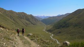 Two guys are hiking by the road in Caucasus mountains. Friends are walking in mountains. going in valley 4K UHD stock footage