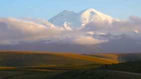 Two guys are hiking to mount Elbrus by the road in Caucasus mountains. Friends are going to mount Elbrus in clouds 4K stock footage
