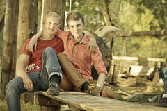 Two guys hugging. Two friendly male mature students outdoors in park sitting on bench. Two guys hugging Royalty Free Stock Photos